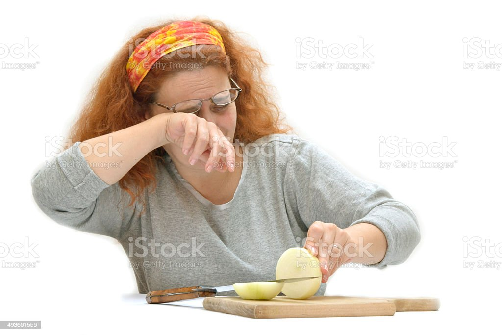 Woman crying while cuts onions on a kitchen board stock photo