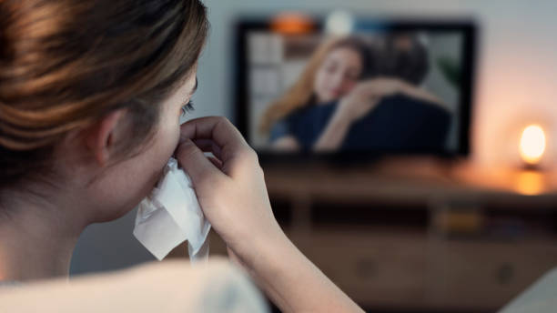 Woman crying while watching tv in the night Woman crying while watching tv in the night crying stock pictures, royalty-free photos & images