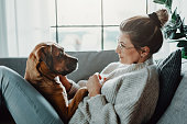 istock Woman cuddles, plays with her dog at home 1215973858
