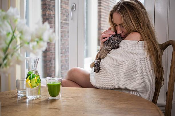 Frau, die eine Katze Kuscheln am Morgen – Foto