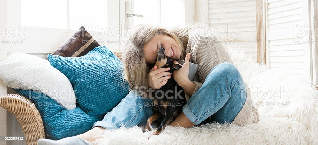 Woman cuddling her dog stock photo