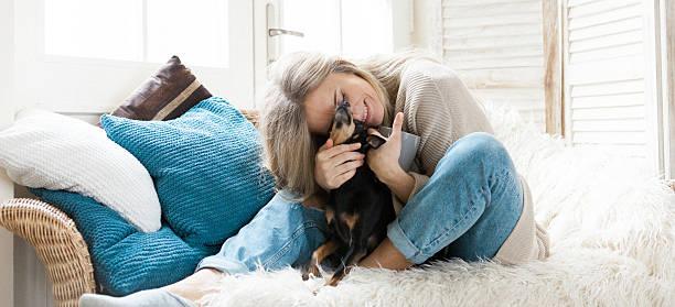 woman cuddling her dog - raumteiler weiß stock-fotos und bilder