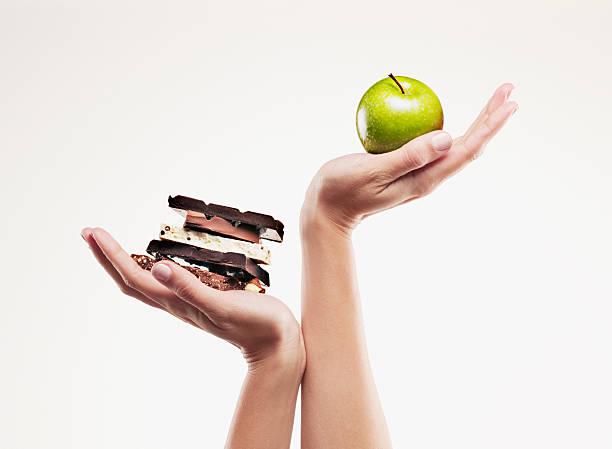 woman cupping green apple above chocolate bars - 不健康飲食 個照片及圖片檔