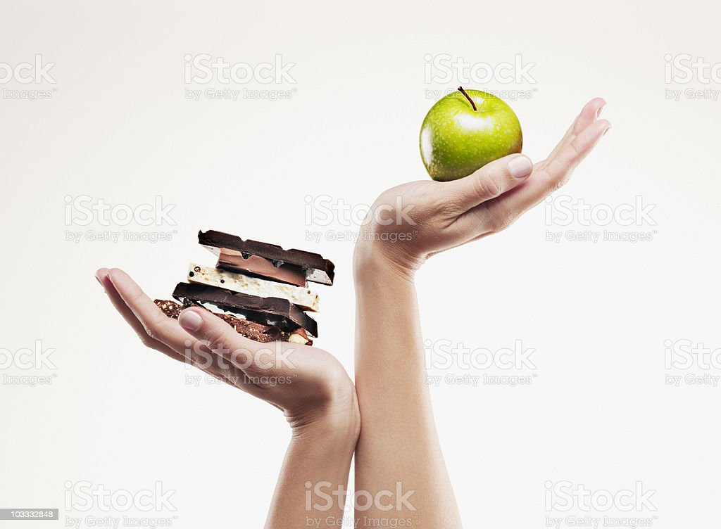 Woman cupping green apple above chocolate bars stock photo