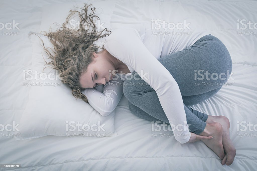Woman curled up in bed stock photo