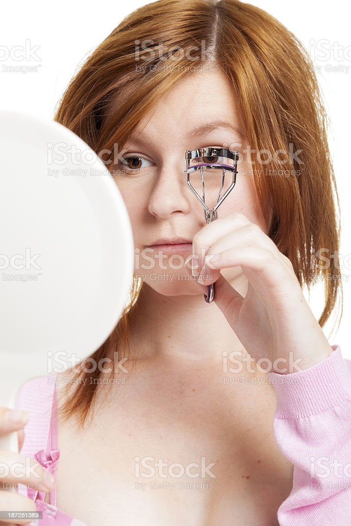 Woman curling her eyelashes stock photo
