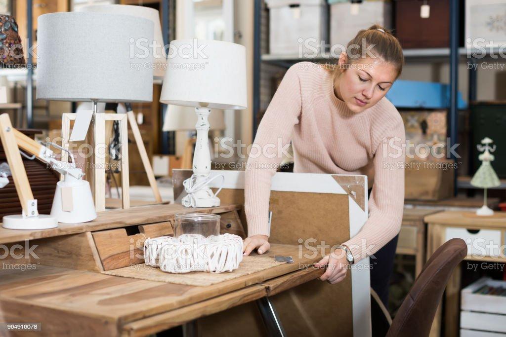 Woman customer choosing wooden dressing table royalty-free stock photo