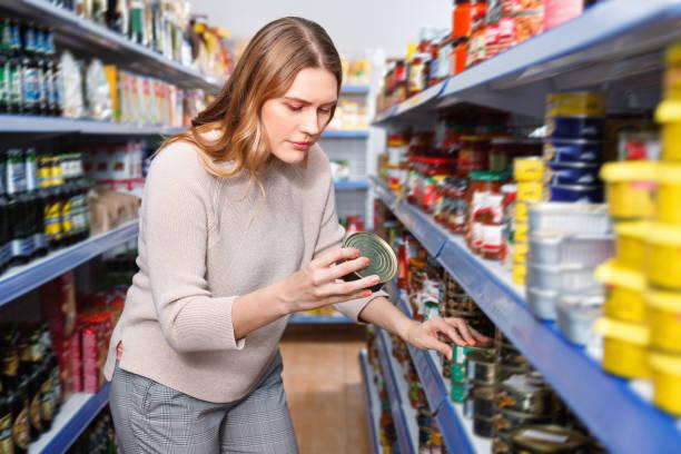 여자 고객 들고 통조림 식품이 게에서 생선 상품 - 통조림 식품 뉴스 사진 이미지