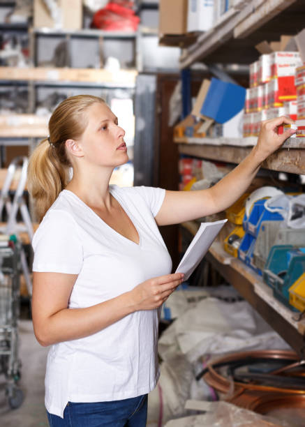 Woman customer  holding  shop list and looking tools at shelves in store stock photo
