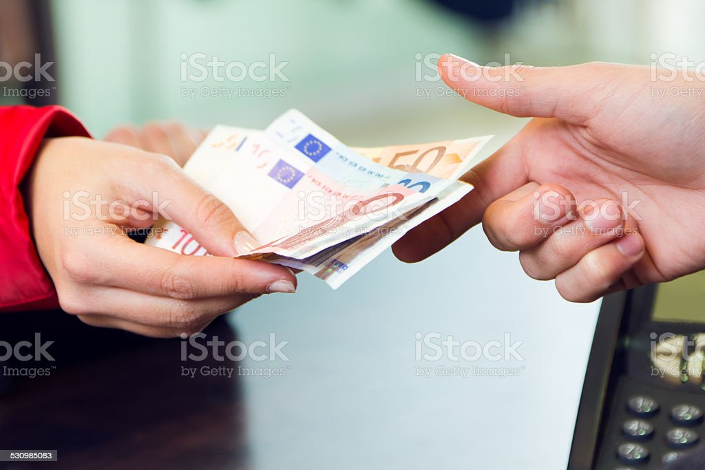 Woman customer paying with money. Hands detail. stock photo