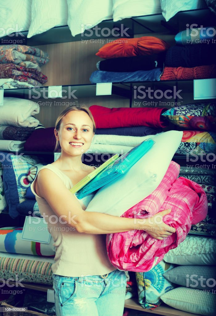 smiling woman customer picking bed cover, pillow, bedding set in...
