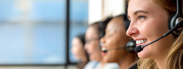 Woman customer service agents working in call center Friendly beautiful caucasian woman telemarketing customer service agent working in call center with multiethnic team call centre photos stock pictures, royalty-free photos & images