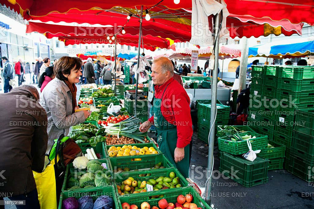 Woman customer talking with owner of Market Stand royalty-free stock photo