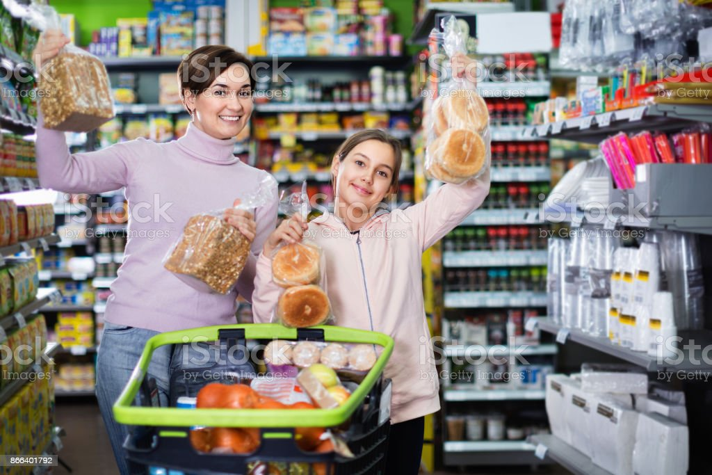 Woman customer with girl looking for tasty bread stock photo