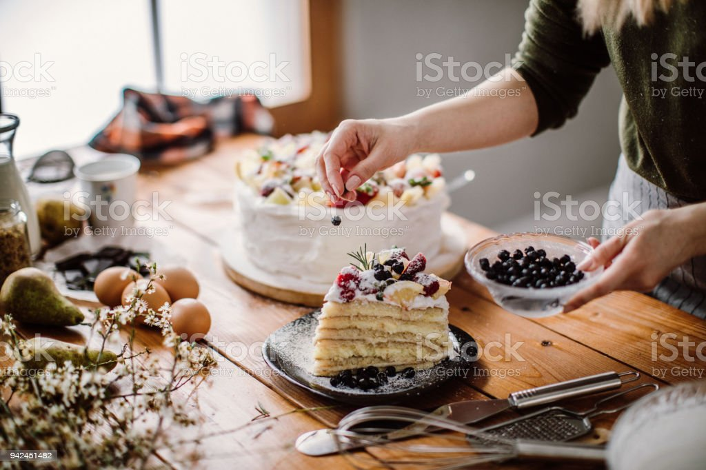 Woman cut a piece of cake for the birthday celebrant stock photo