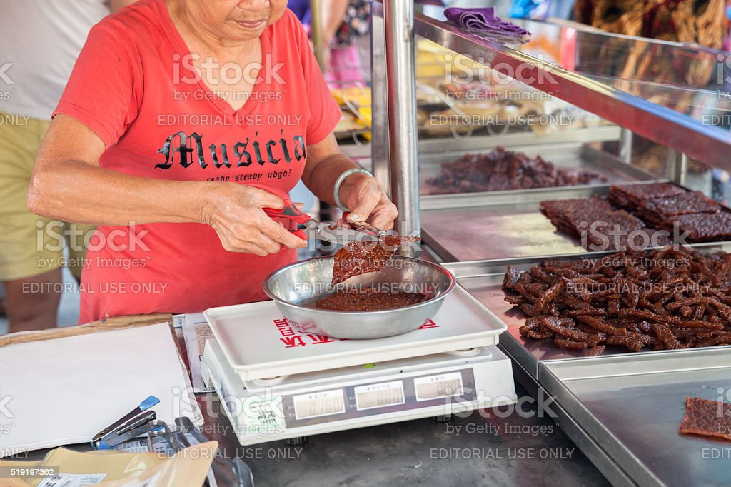 Woman cut and weigh Chinese dried pork stock photo