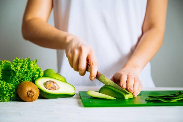 vrouw snijd de avocado. gezonde voeding-concept. ingrediënten voor smoothies - rijp voedselbereiding stockfoto's en -beelden