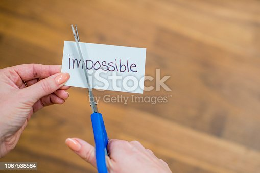 A woman uses scissors to cut the first two letters out of the word impossible, to create a handwritten message of 'possible'.