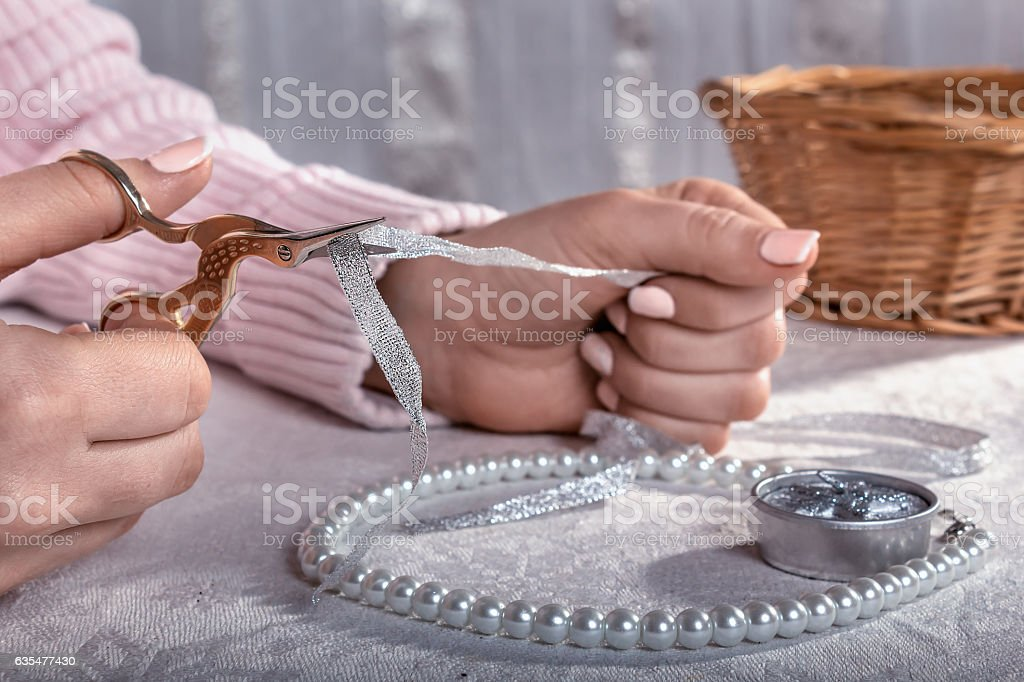 Woman cuts the tape with scissors and make decorations stock photo