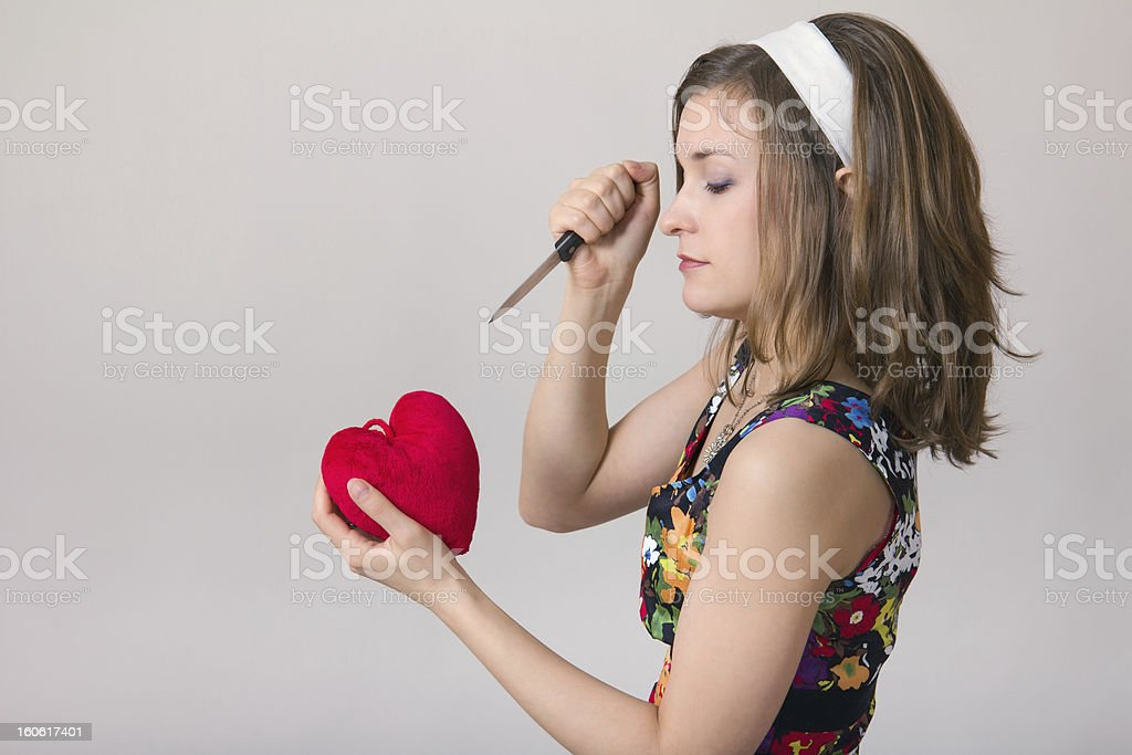 woman cutting a heart toy with knife stock photo