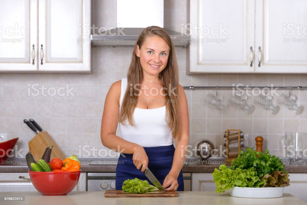 Woman cutting a salad from greenery in kitchen stock photo