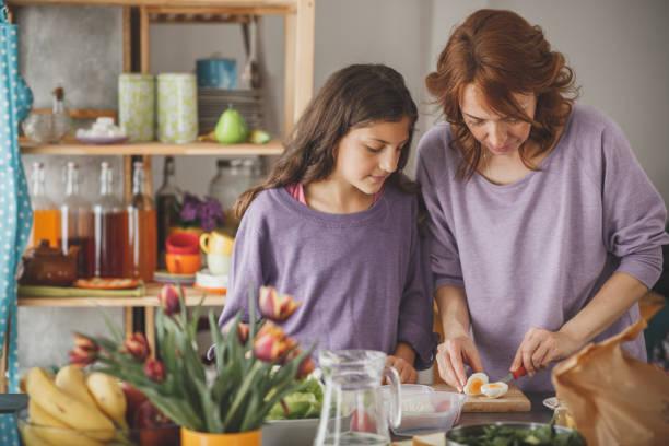 frau schneidet gekochtes ei während der zubereitung einer gesunden mahlzeit - lila mädchen zimmer stock-fotos und bilder