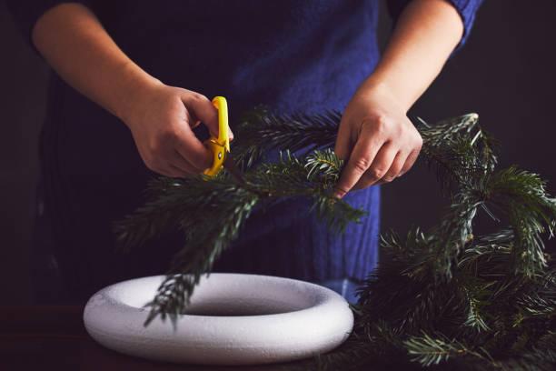 frau schneiden zweig für die dekoration von der weihnachtskranz - eco bastelarbeiten stock-fotos und bilder