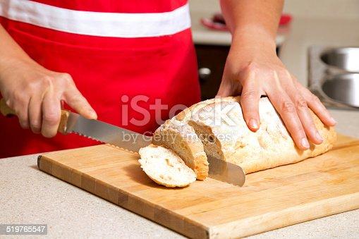 istock woman cutting bread 519765547