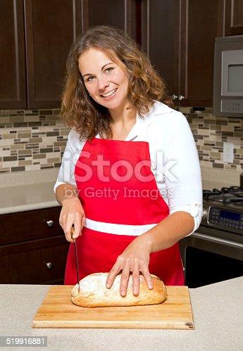 istock woman cutting bread 519916881