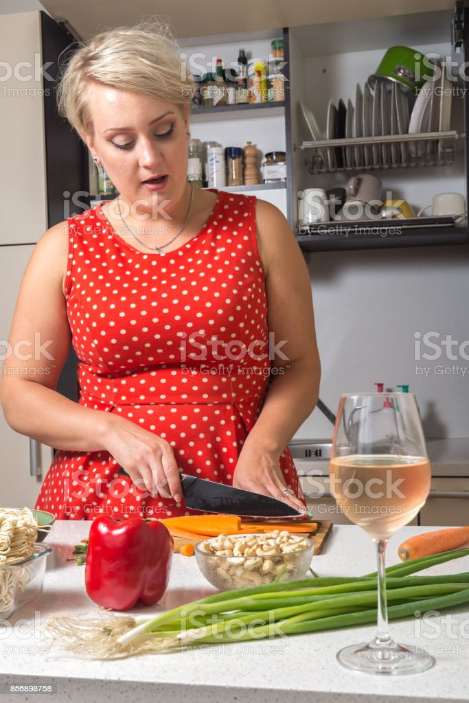 Woman cutting carrot and preparing for vegetable wok stock photo