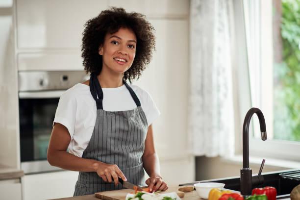 Frau schneiden Karotten in der Küche zu Hause. – Foto