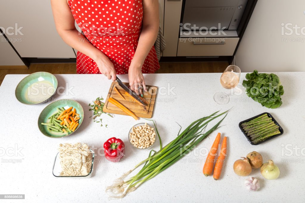Woman cutting carrots and preparing food stock photo