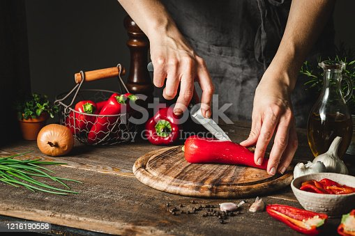 Close-up of a woman hands cutting red peppers on a chopping board. Woman chef preparing red pepper soup in kitchen.
