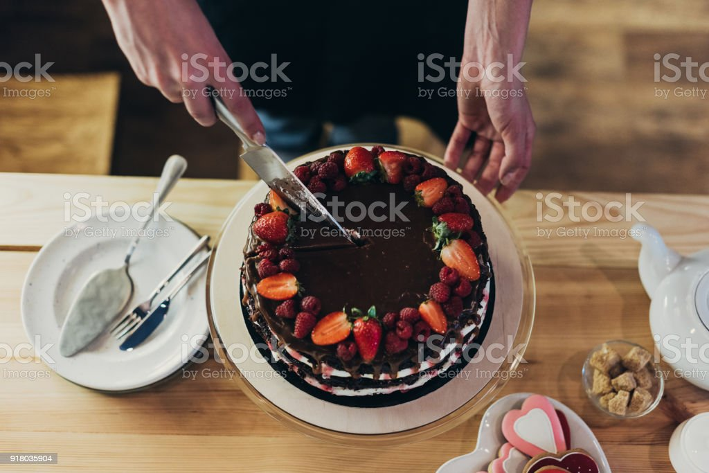 woman cutting chocolate cake stock photo