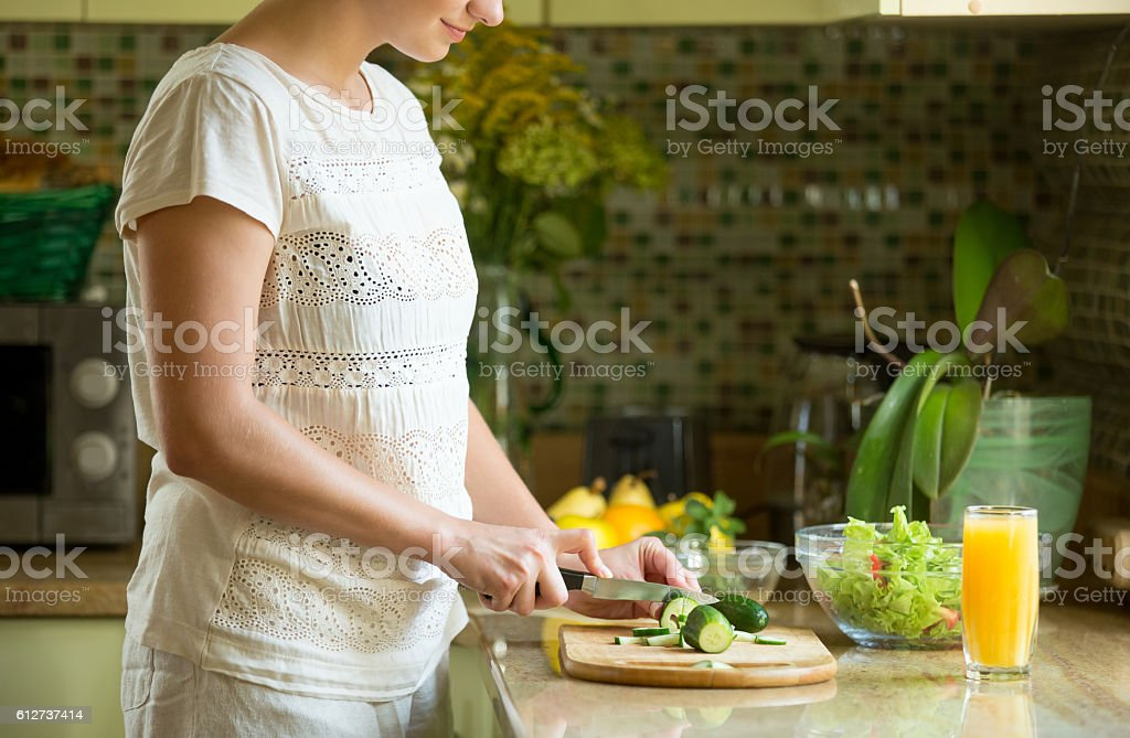 Woman cutting cucumbers for a salad on the kitchen stock photo
