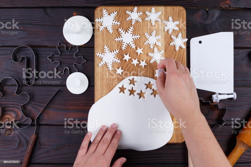 Woman cutting decorations in form of stars and snowflakes of con stock photo