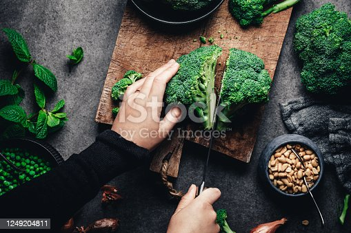 Hands of female cutting broccoli on kitchen counter. Point of view of woman chopping fresh broccoli with kitchen knife.