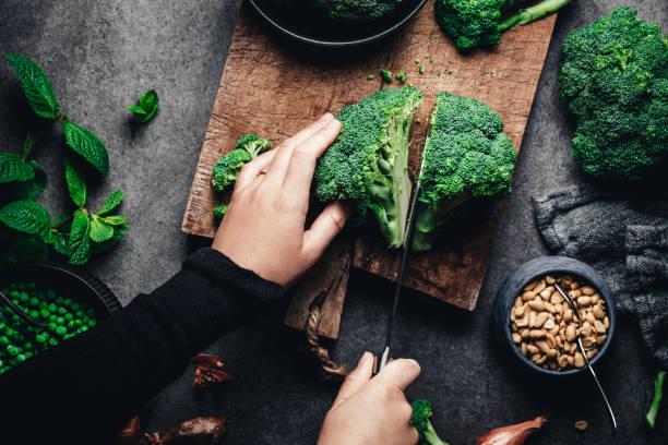 kobieta cięcia świeżych brokułów - kapustowate zdjęcia i obrazy z banku zdjęć