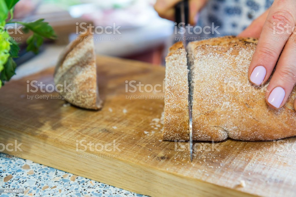Woman cutting fresh homemade bread on wooden board royalty-free stock photo
