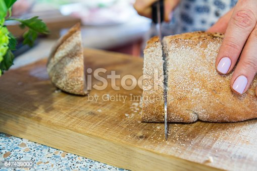 Woman Cutting Fresh Homemade Bread On Wooden Board Stock Photo & More Pictures of Adult