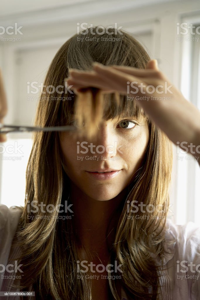 Woman cutting hair with scissors, close-up royalty free stockfoto