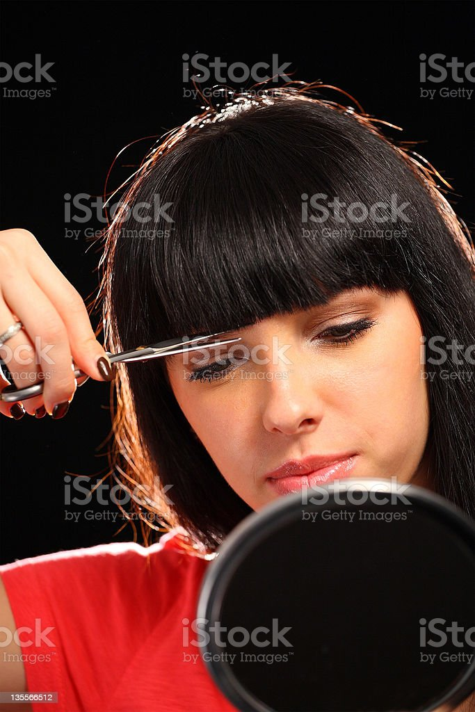 Woman cutting her hair stock photo