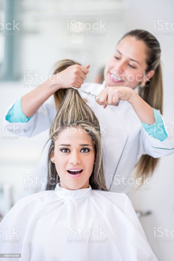 Woman cutting her hair short at the hairdresser stock photo