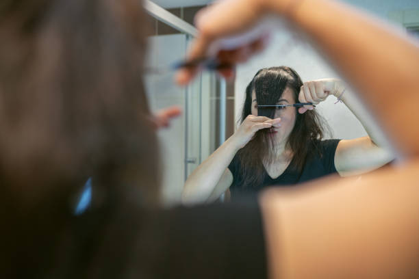 woman cutting her own hair in quarantine days - covid hair imagens e fotografias de stock