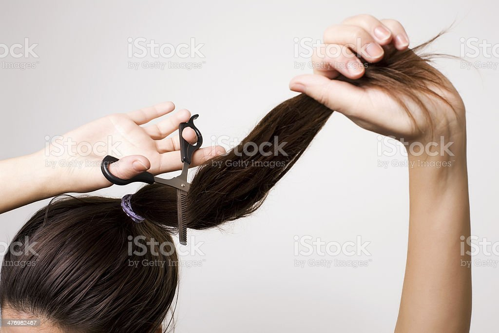 Woman cutting her ponytail stock photo
