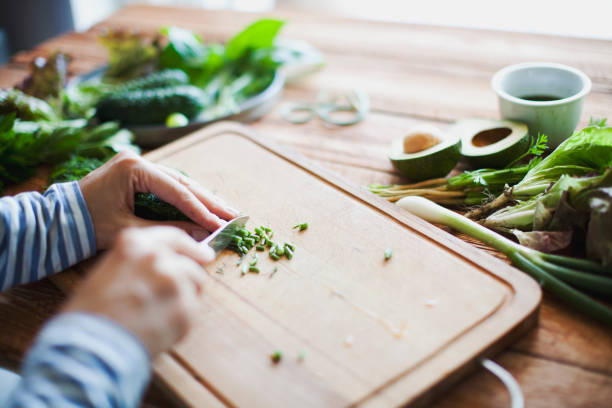 Woman cutting herbs and vegetables stock photo