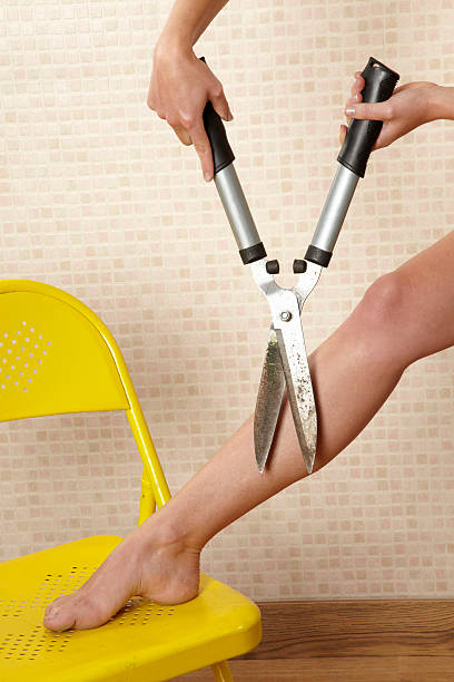 Woman cutting leg hair with garden sheers stock photo