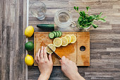 female hands cutting  lemon for detox water. Ingredients for infused water on a wooden board. Top view. Detox. Healthy drink . Weight loss dieting concept. Process of preparing energy cocktail