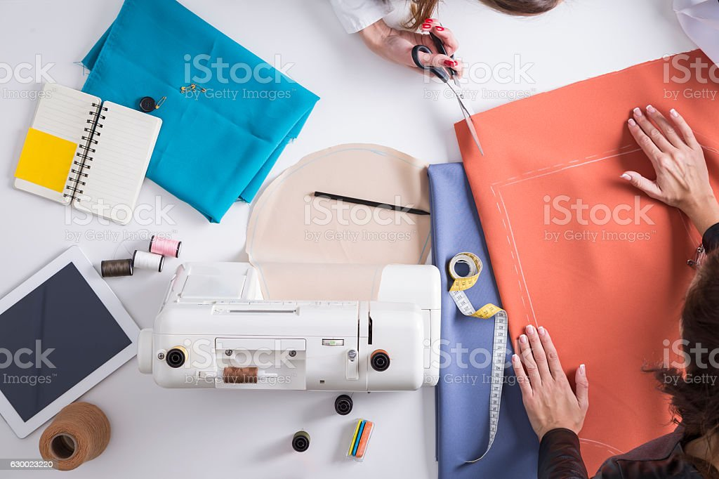 Woman cutting material her colleague is holding stock photo