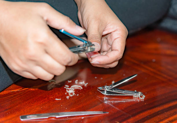 Woman cutting nails using nail clipper - close up on activity cutting. Woman cutting nails using nail clipper - close up on activity cutting at home. pedicure manicure men beauty spa stock pictures, royalty-free photos & images